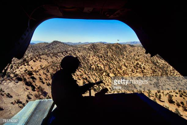 On the border of Pakistan in the Pashtun tribal zone of Waziristan this American soldier flies over the zone with his submachine gun ready to shoot...