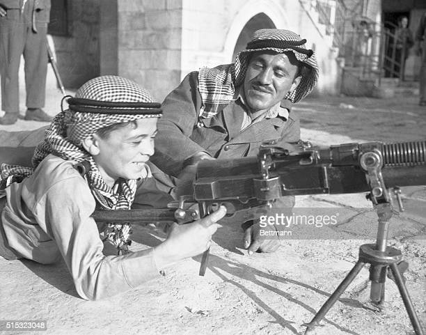 On the day before the State of Israel was proclaimed a young Palestinian boy looks at an Arab soldier's machine gun