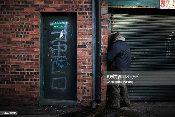 On the day that Britain officially enters a recession a homeless man urinates in the street on January 23 2009 in Liverpool United Kingdom Figures...