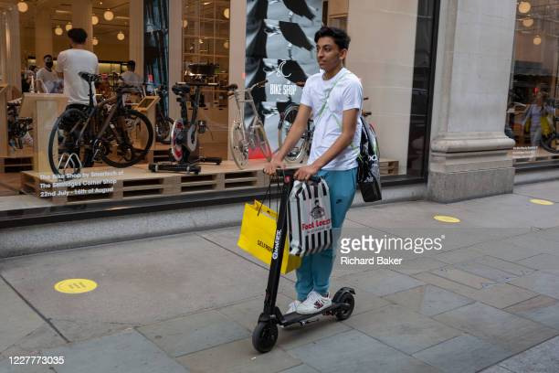 On the day that covid pandemic guidelines for shoppers in England mean that the wearing of face coverings in shops is mandatory, a shopper rides his...