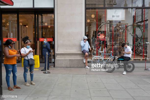 On the day that covid pandemic guidelines for shoppers in England mean that the wearing of face coverings in shops is mandatory, shoppers wearing...