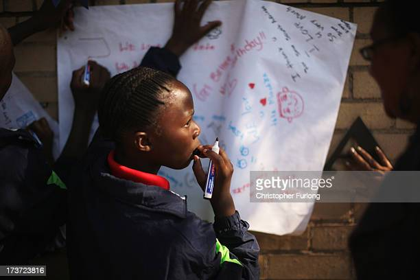 On the eve of Nelson Mandela's 95th birthday a girl from a local orphange writes birthday messages outside the MediClinic Heart Hospital on July 17...