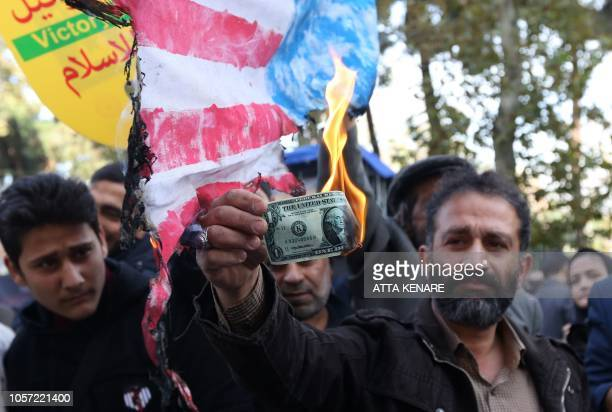 On the eve of renewed sanctions by Washington An Iranian protester burns a dollar banknote during a demonstration outside the former US embassy in...