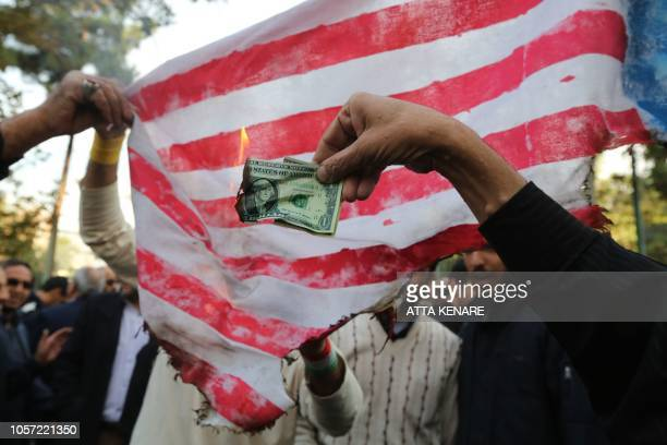 On the eve of renewed sanctions by Washington Iranian protesters burn a dollar banknote and a US makeshift flag during a demonstration outside the...