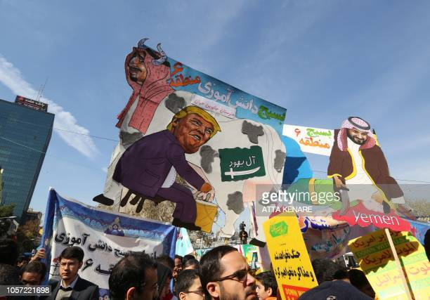 On the eve of renewed sanctions by Washington Iranian protesters carry placards that mock President Donald Trump Saudi Arabia's King Salman and Crown...
