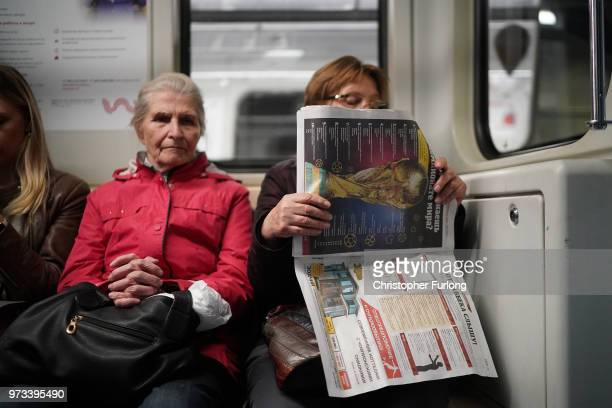 On the eve of the World Cup a woman reads a newspaper with The World Cup pictured on the front page on June 13 2018 in Moscow Russia On the eve of...