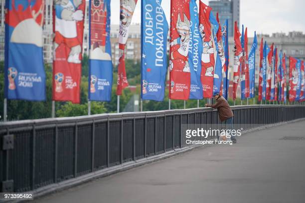 On the eve of the World Cup people relax as they walk across a bridge festooned with World Cup flags on June 13 2018 in Moscow Russia On the eve of...