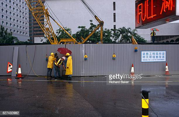 On the eve of transfer of law in Hong Kong from the UK to China, construction workers in Central Hong Kong carry on their tasks during a monsoonal...