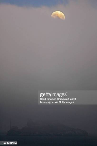 On the evening 8/27 before a early morning total eclipse the full moon slowly made its way through the summer fog over Alcatraz Island Editor note...