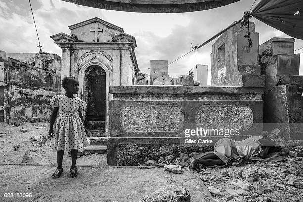 PRINCE HAITI JANUARY 12 2015 On the fifth anniversary of the devastating earthquake a young child stands to the side of her mourning mother who lies...