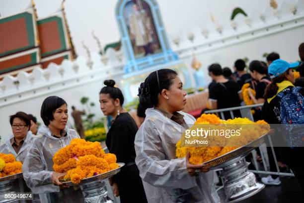 On the first anniversary of Thailand's King Bhumibol Adulyadej's death thousands of Thai mourners queue up outside the gates of the royal palace in...