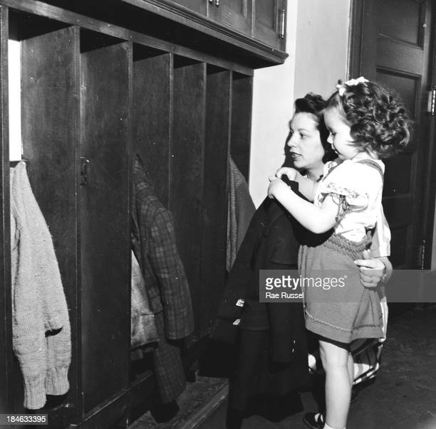 On the first day of school a nursery school teacher helps a young girl get her coat in her cubbyhole Madison New Jersey 1948 The picture was taken...
