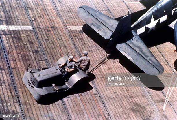 On the flight deck of the USS Monterey two crewmen use a flight tractor to reposition an F6F3 'Hellcat' fighter Pacific Ocean late 1943