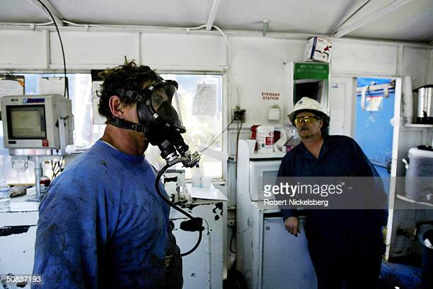 On the floor of a natural gas drilling rig a roughneck goes through a hydrogen sulfide gas safety drill with an oxygen mask May 8 2004 eight miles...