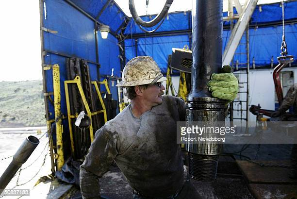 On the floor of a natural gas drilling rig a roughneck moves 100foot section of drilling pipe May 7 2004 eight miles north of Evanston Wyoming The...