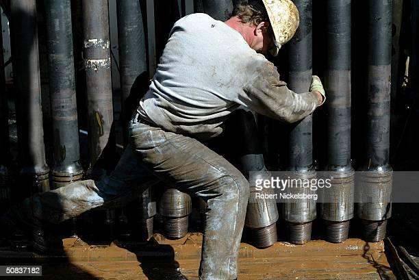 On the floor of a natural gas drilling rig a roughneck moves a 100foot section of drilling pipe May 7 2004 eight miles north of Evanston Wyoming The...