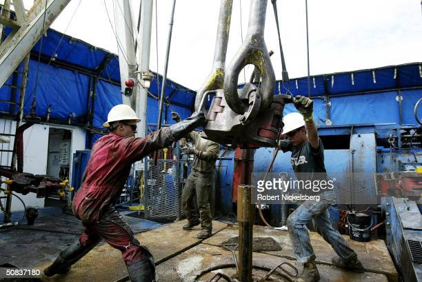 On the floor of a natural gas drilling rig roughnecks move 25ton blocks over a section of drilling pipe May 8 2004 eight miles north of Evanston...