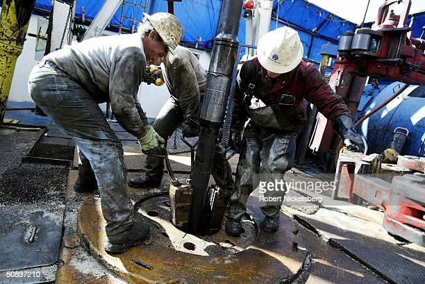 On the floor of a natural gas drilling rig roughnecks remove a slip around a 100foot section of drilling pipe so it can be lowered May 7 2004 eight...