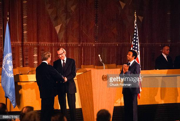 On the floor of the United Nations American President Jimmy Carter shakes hands UN Secretary General Kurt Waldheim as US Ambassador Andrew Young...