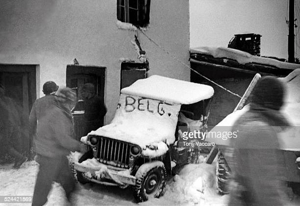 On the fringes of the Battle of the Bulge a snowcovered jeep can be seen with the word 'Belg' on its windshield Ardennes World War II December 1944