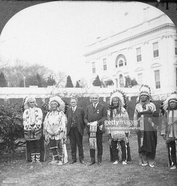 On the grounds of the White House American President Warren G Harding and Commissioner of the Bureau of Indian Affairs Charles Henry Burke pose with...