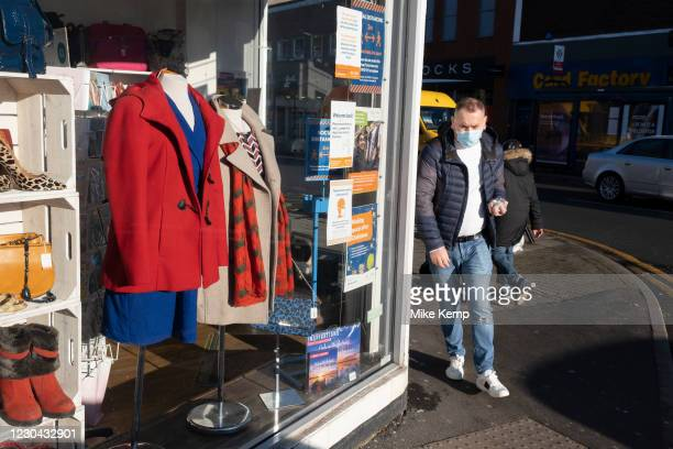 On the last day of the year, people pass a closed charity shop wearing masks along Kings Heath High Street, as many shops remain closed, with...