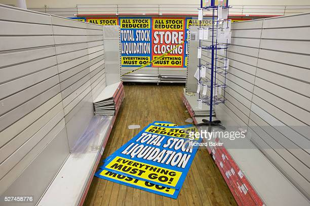 On the last day of trading surrounded by empty shelves and shop fittings sheets of closing down posters are seen lying on the shop floor in the...