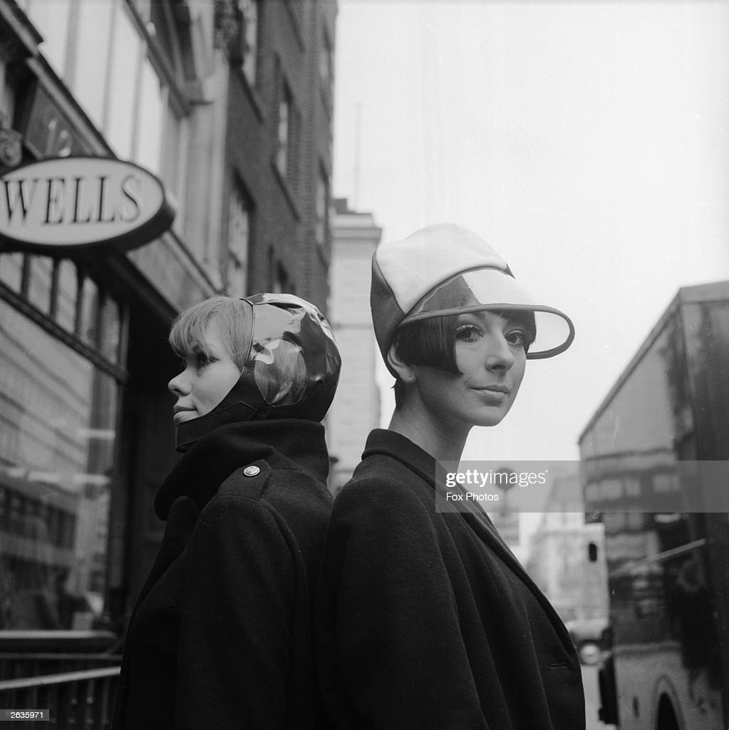 On the left, a model wears a vinyl helmet with perspex earphone, called 'Sea Diver', and on the right is 'Seaspray', a red and white racing cap with a sun-protecting visor. Both are from designer Edward Mann's Spring Collection, being modelled in London.