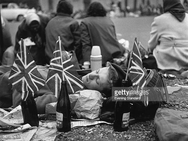 On the morning of Princess Margaret's wedding a young man sleeps on the pavement surrounded by union jack flags stuck into empty beer bottles