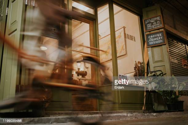 on the move, passing coffee shop in the evening - closed stock pictures, royalty-free photos & images