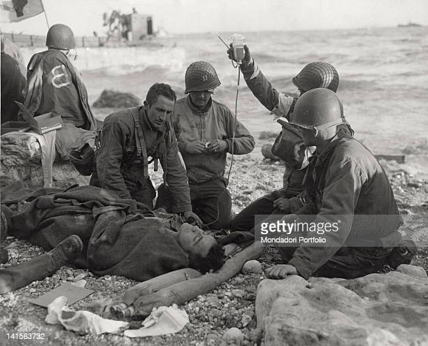 On the Normandy coast on the beach codenamed 'Omaha Beach' Red Cross men give a blood transfusion to an injured man ViervillesurMer 6th June 1944