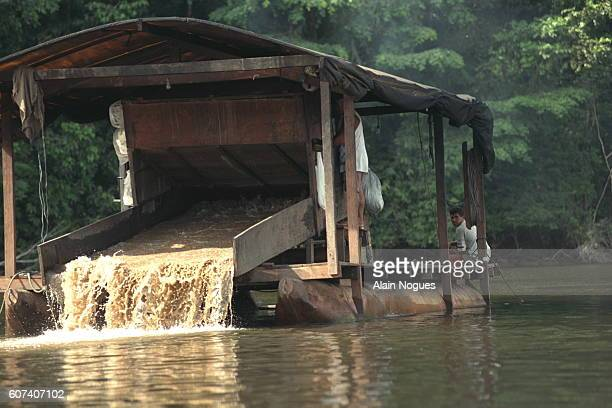 On the Oyapok, a suction dredger pours mud from the river bed. The gold specks are retained.