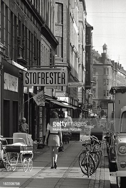 On the pavement of a street full of shops of Copenhagen a girl is wearing a mini skirt and is walking while in the background another woman is...