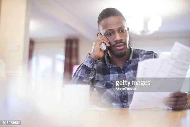 on the phone to his bank - car insurance stock pictures, royalty-free photos & images