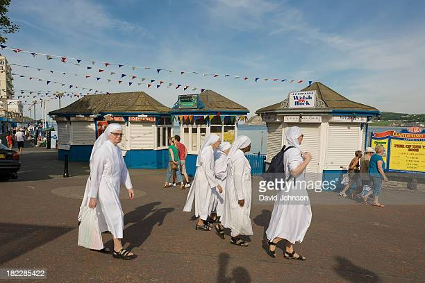 On the promenade at Llandudno on the North Wales coast, a group of Nuns are taking in the local attractions.