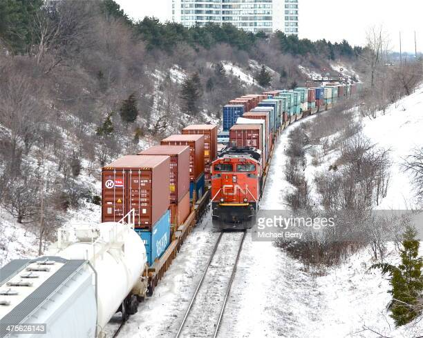 CONTENT] On the right a CN locomotive is pushing a CN intermodal train eastwards while another CN freight passes westwards