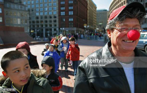 On the right fourth grade teacher Rick Andrew from the Quincy Elementary School wearing a big red nose walked from Chinatown to Boston City Hall...