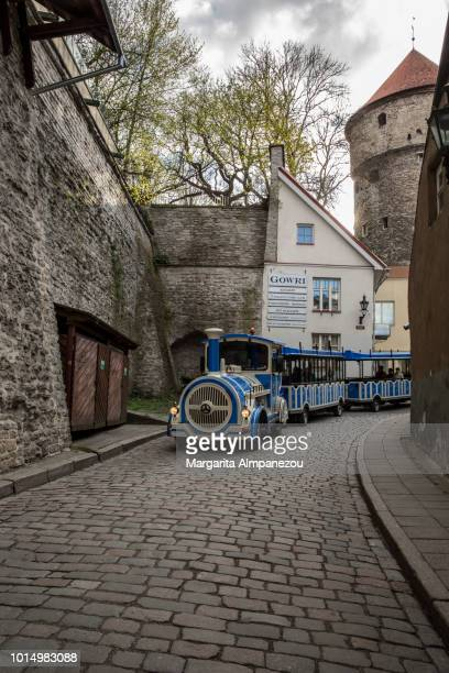 On the Road: Blue touristic train-bus is moving on a pedestrian road inside the historic center of Tallinn