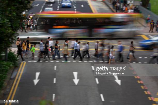 On the Road: Busy intersection in Singapore with pedestrians and a bus crossing