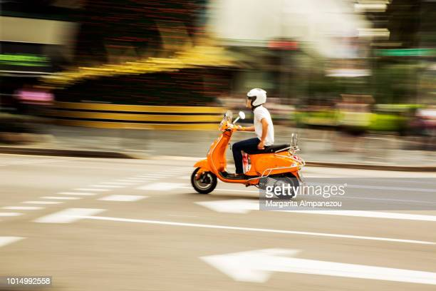 On the Road: Panning on an orange scooter driving the road in Singapore