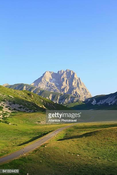 on the road to campo imperatore. in the background the corno grande , the top of the gran sasso d'italia mountain. - parco nazionale d'abruzzo foto e immagini stock