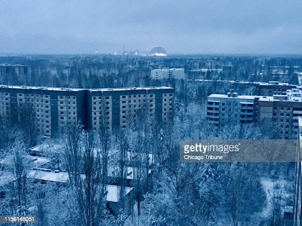 On the roof of a 16story apartment building in Pripyat at sunset a visitor can see what remains of the abandoned town The only light comes from the...