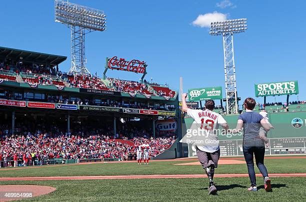 On the second anniversery of the Boston Marathon bombings survivor Jeff Bauman with his wife and their child accompanying him acknowledges the cheers...
