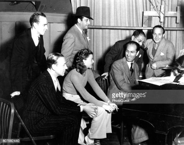 On the set of the film 'Shall We Dance' George Gershwin plays piano with from left dance director Hermes Pan actors Fred Astaire and Ginger Rogers...