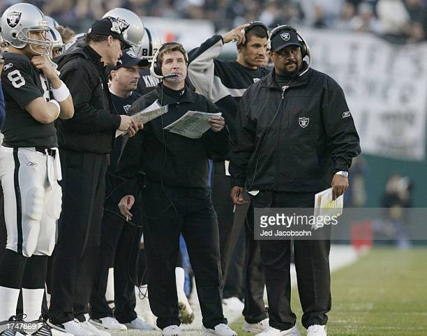On the sideline Oakland Raiders offensive coordinator Marc Trestman talks with firstyear head coach Bill Callahan and RB coach Skip Peete during the...
