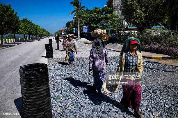 On the Strand road in Mawlamyine a group of women are carrying basket of stones on their head while working at repairing the road