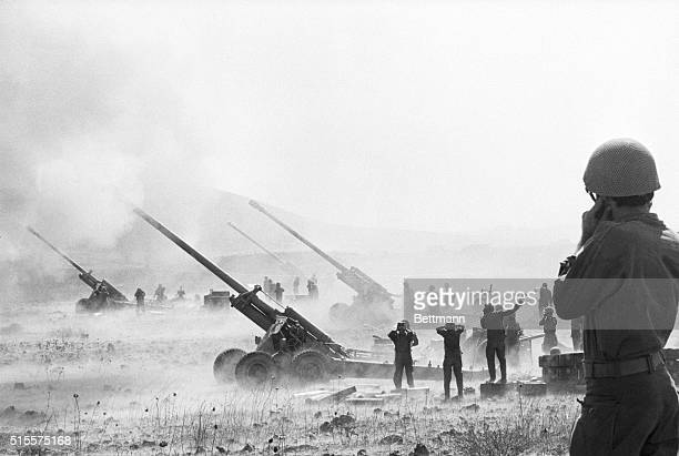 Acrid fumes and smoke fill the air and Israeli artillerymen hold their ears while laying down barrage on Syrian positions here October 12 The guns...