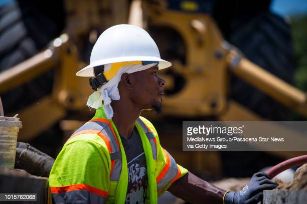On the third day of a heat wave Demetrice Brown waits in a ditch for a backhoe to lift pipe as Pasadena Water and Power changes out the water main on...