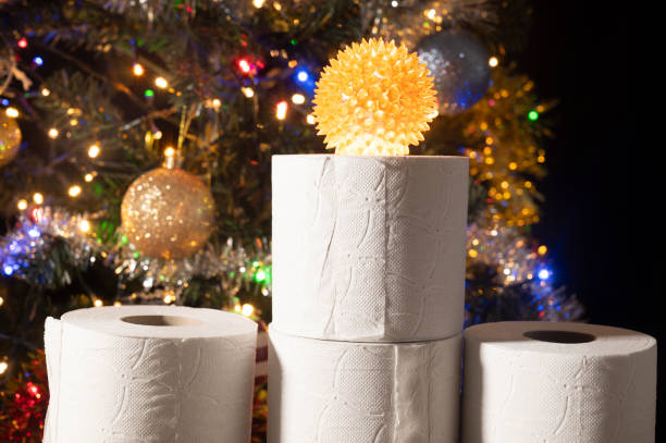 On the toilet paper rolls is a spiky ball that may represent the coronavirus. Christmas tree decorated with colourful lights in the background.