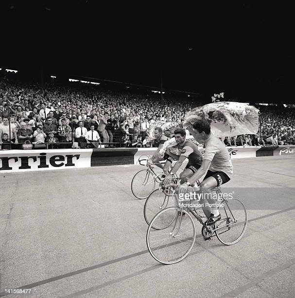 On the track of Parc des Princes Velodrome the three winning cyclists at the end of the Tour de France are celebrated by the crowd of the inner...